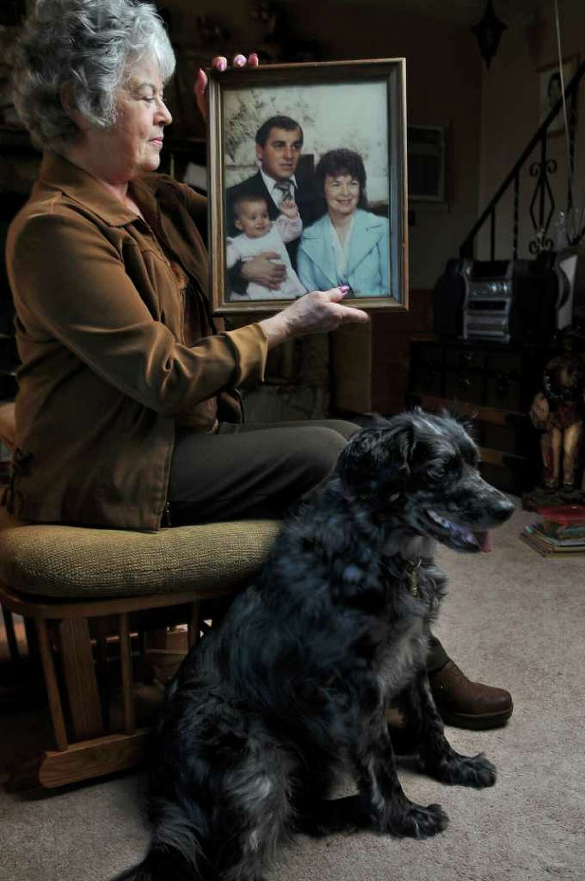 Margaret Porto LaMori holds a 1984 photograph of herself with her late husband Peter E. Porto and their grandchild Krishna, on Tuesday Dec. 13, 2011 in Scotia, N.Y. Peter died in 2006 from illness related to exposure to asbestos. Her dog Boo sits next to her. (Philip Kamrass / Times Union)