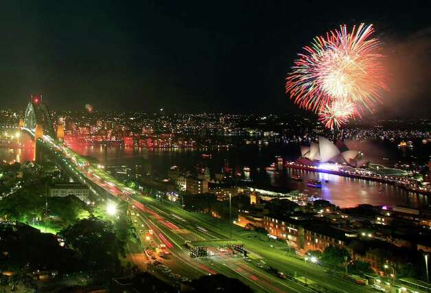 Fireworks burst over the Sydney Opera House, rigfht, as New Year's celebrations begin in Sydney, Saturday, Dec. 31, 2011. (AP Photo/Rick Rycroft) Photo: Rick Rycroft