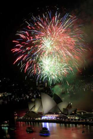 Fireworks burst over Sydney Opera House as New Year's celebrations begin in Sydney, Australia, Saturday, Dec. 31, 2011. (AP Photo/Rick Rycroft) Photo: Rick Rycroft