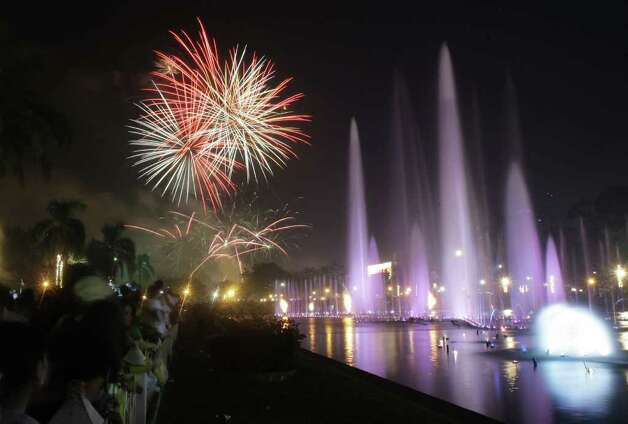 Filipinos watch a fireworks and water fountain display as they welcome the New Year at Manila's Rizal Park, Philippines on Sunday Jan. 1, 2012. More than 200 people have been injured by illegal firecrackers and celebratory gunfire in the Philippines despite a government scare campaign against reckless New Year revelries, officials recently said. (AP Photo/Aaron Favila) Photo: AARON FAVILA