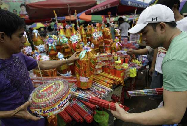A Filipino man buys firecrackers at a makeshift stand in downtown Manila, Philippines on Saturday Dec. 31, 2011. More than 200 people have been injured by illegal firecrackers and celebratory gunfire in the Philippines despite a government scare campaign against reckless holiday revelries, officials said. (AP Photo/Aaron Favila) Photo: Aaron Favila
