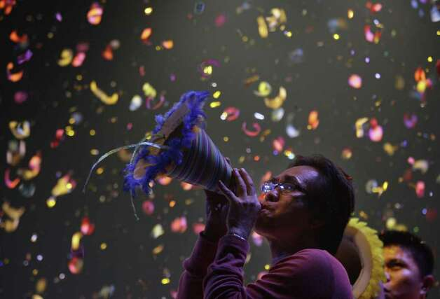 Confetti drops as a Filipino blows his paper horn as they welcome the New Year at Manila's Rizal Park, Philippines on Sunday Jan. 1, 2012. More than 200 people have been injured by illegal firecrackers and celebratory gunfire in the Philippines despite a government scare campaign against reckless New Year revelries, officials recently said. (AP Photo/Aaron Favila) Photo: AARON FAVILA