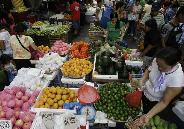 A Filipino woman receives her change as she buys round fruits at a makeshift stand in downtown Manila, Philippines on Saturday Dec. 31, 2011. Many Filipinos believe that having 12 round fruits of different kinds (or pieces) on the family table will bring good luck during the New Year. (AP Photo/Aaron Favila) Photo: Aaron Favila