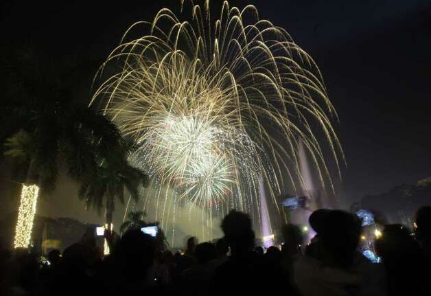 Filipinos watch a fireworks display as they welcome the New Year at Manila's Rizal Park, Philippines on Sunday Jan. 1, 2012. More than 200 people have been injured by illegal firecrackers and celebratory gunfire in the Philippines despite a government scare campaign against reckless New Year revelries, officials recently said. (AP Photo/Aaron Favila) Photo: AARON FAVILA