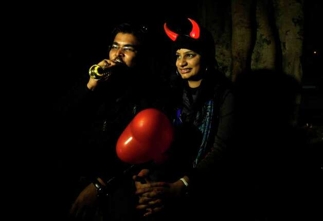 An Indian couple sport illuminated horns as they celebrate on New Year's Eve, in New Delhi, India, Friday, Dec. 31, 2011.  (AP Photo/ Mustafa Quraishi) Photo: Mustafa Quraishi / AP