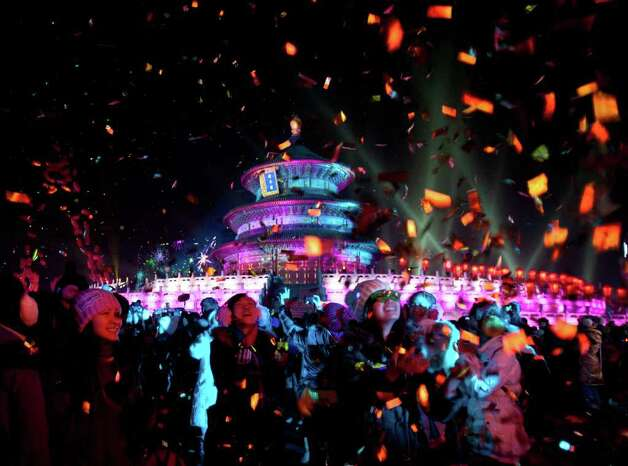 Visitors are  showered by confetti as they celebrate a light show at the Temple of Heaven during the New Year Countdown Ceremony in Beijing, China, Sunday, Jan 1 2012. (AP Photo/Andy Wong) Photo: Andy Wong / AP