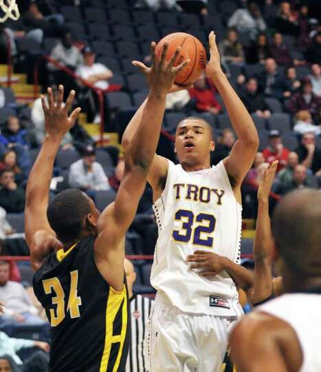 Troy's #32 Javion Ogunyemi shoots over Henniger's #34 Marquies Young, left, during Saturday's game a