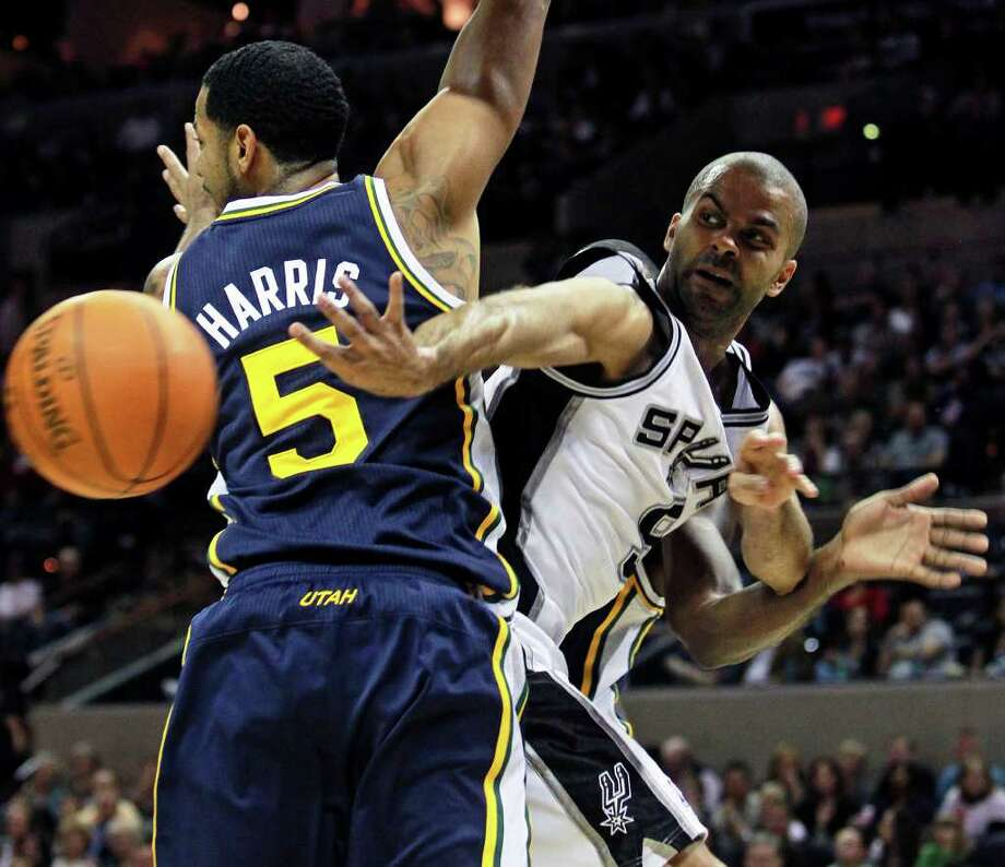 Spurs guard Tony Parker passes under the bucket around Devin Harris as the Spurs play the Utah Jazz at the AT&T Center on December 31, 2011 Tom Reel/Staff Photo: TOM REEL, Express-News / © 2011 San Antonio Express-News  MAGS OUT; TV OUT; NO SALES; SAN ANTONIO OUT; AP MEMBERS ONLY; MANDATORY CREDIT; EFE OUT