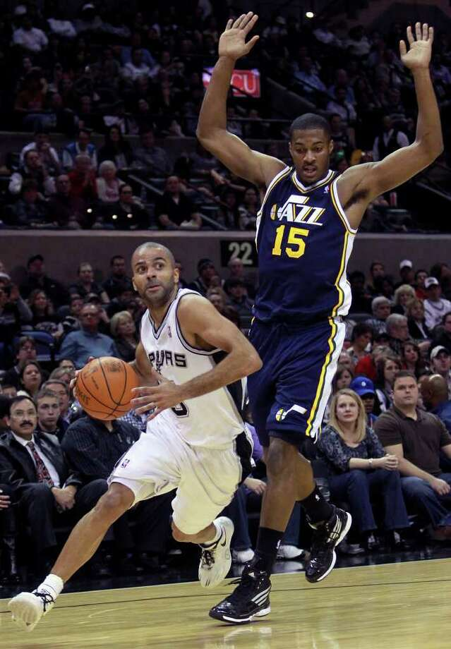 Tony Parker slips by Derrick Favors as the Spurs play the Utah Jazz at the AT&T Center on December 31, 2011 Tom Reel/Staff Photo: TOM REEL, Express-News / © 2011 San Antonio Express-News  MAGS OUT; TV OUT; NO SALES; SAN ANTONIO OUT; AP MEMBERS ONLY; MANDATORY CREDIT; EFE OUT