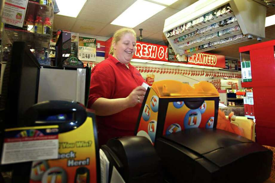 "In this Dec. 31, 2011, photo, Amber Wallenstein, a 31-year-old clerk at the Freedom Value Center convenience store and gas station in Sioux Falls, S.D., rings up a Powerball ticket for a customer. The price for Powerball tickets is set to double Jan. 15. ""I don't think anybody knows about it yet,"" Wallenstein said of the price hike. ""But they'll still pay for it."" (AP Photo/Amber Hunt) Photo: Amber Hunt"