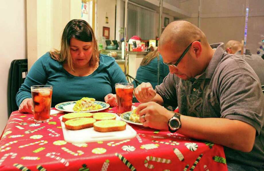 Rachel (left) and her husband Josue pray before dinner Thursday Dec. 22, 2011 at their home. Photo: EDWARD A. ORNELAS, SAN ANTONIO EXPRESS-NEWS / © SAN ANTONIO EXPRESS-NEWS (NFS)