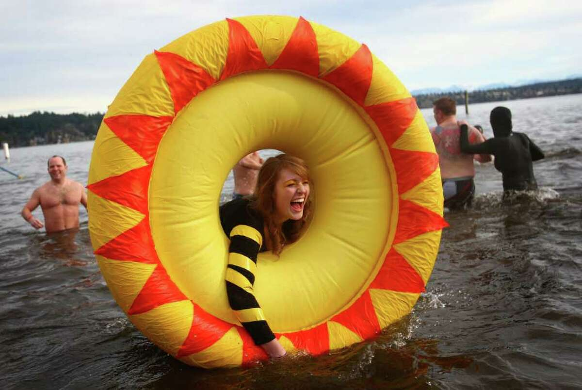 Laura D'Asaro holds onto an inflatable sun as she braves the 49-degree Lake Washington water during the annual Polar Bear Plunge at Matthews Beach in Seattle on Sunday.