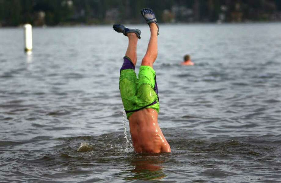 A participant goes upside down in Lake Washington during the 10th annual Polar Bear Plunge at Matthews Beach in Seattle. Photo: JOSHUA TRUJILLO / SEATTLEPI.COM