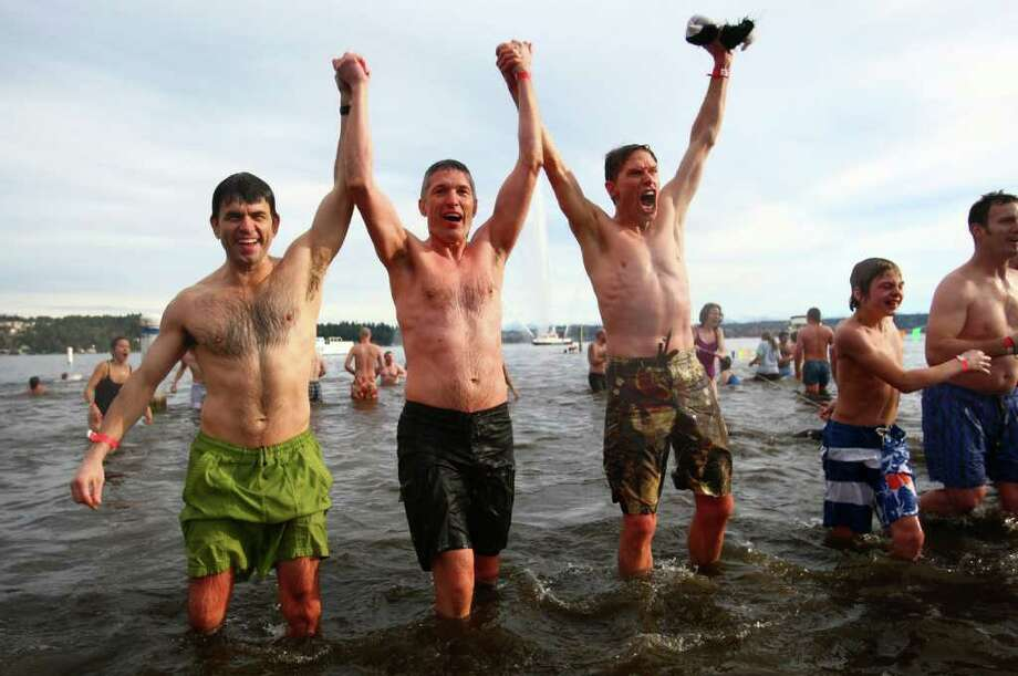 Participants raise their arms in Lake Washington during the annual Polar Bear Plunge at Matthews Beach in Seattle. Photo: JOSHUA TRUJILLO / SEATTLEPI.COM