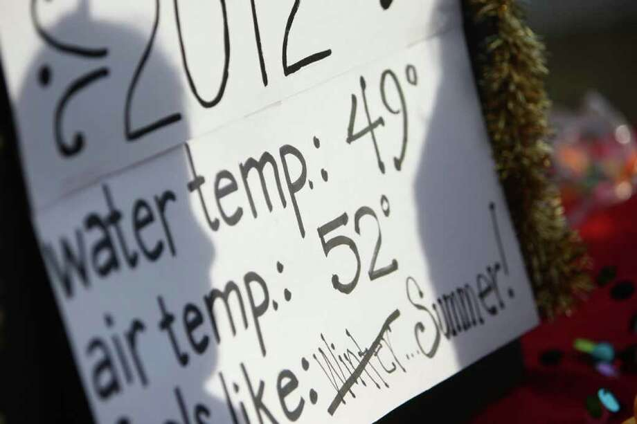 A sign shows the water and air temperature during the annual Polar Bear Plunge at Matthews Beach in Seattle. Photo: JOSHUA TRUJILLO / SEATTLEPI.COM