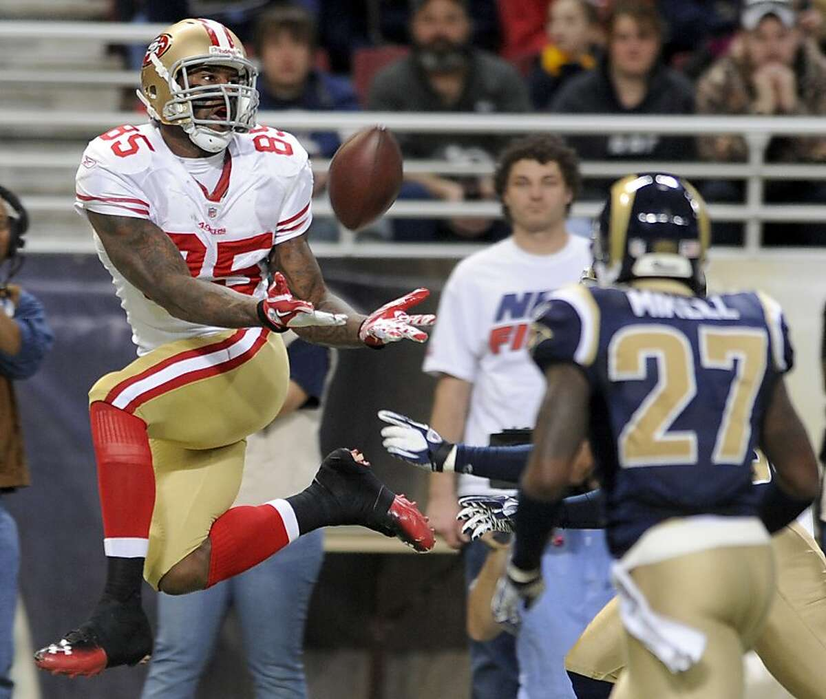 San Francisco 49ers tight end Vernon Davis, left, catches a 44-yard pass as St. Louis Rams safety Quintin Mikell (27) defends during the second quarter of an NFL football game Sunday, Jan. 1, 2012, in St. Louis. (AP Photo/L.G. Patterson)