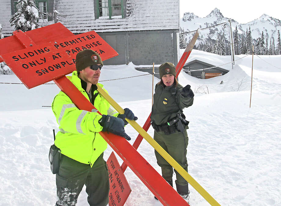 In this photo taken Dec. 31, 2011, Margaret Anderson, right, a law enforcement ranger at Mount Rainier National Park works at the Paradise snow play area in Mount Rainier, Wash. Anderson was shot and killed on New Years Day sparking the closure of the park and a massive manhunt for the suspect. (AP Photo/The News Tribune, Dean J. Koepfler)