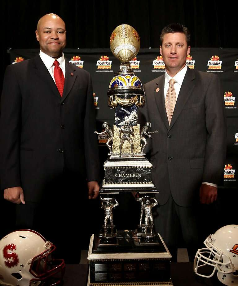 Stanford head coach David Shaw, left, poses with Oklahoma State head coach Mike Gundy during a news conference, Sunday, Jan. 1, 2012, in Scottsdale, Ariz., as they prepare their respective teams for the Fiesta Bowl NCAA college football game, on Jan. 2. (AP Photo/Rick Scuteri) Photo: Rick Scuteri, Associated Press