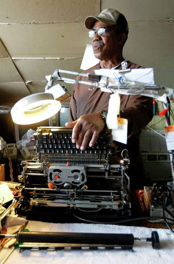 "Edward ""Smitty"" Smith opens up a typewriter to repair, something he's been doing for 44 years at his Universal Typewriter Shop on Dowling in the city's Third Ward. Photo: Karen Warren / © 2011 Houston Chronicle"