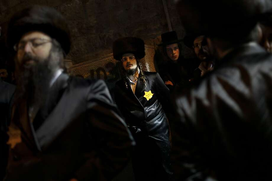 Orthodox Jewish men, wearing a Star of David patch similar to those the Nazis forced Jews to wear, attend a rally in Jerusalem's Mea Shearim neighborhood, Saturday, Dec. 31, 2011. Thousands of ultra-Orthodox Jews gathered to rally for the right to protect their way of life. (AP Photo/Bernat Armangue) Photo: Bernat Armangue, Associated Press