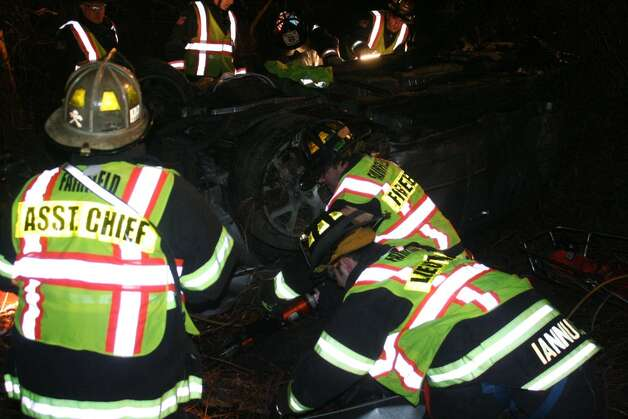 Two people are dead after their car careened off the highway and over a steep embankment on Interstate 95 northbound near Exit 19 shortly after 3 a.m. Sunday. (Photo/Fairfield Fire Department) Photo: Contributed Photo / Connecticut Post Contributed
