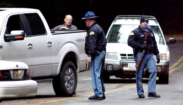 A Washington State Patrol trooper carries a gun as he checks out vehicles leaving Mount Rainier National Park, Sunday, Jan. 1, 2012 in Washington State. Park rangers were turning away incoming visitors after a National Parks Service Ranger was shot and killed at the park Sunday morning. (AP Photo/Ted S. Warren) / AP2012