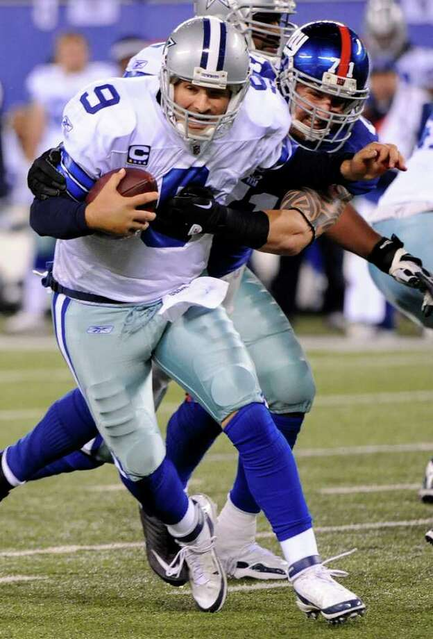 Dallas Cowboys quarterback Tony Romo (9) evades a tackle by New York Giants defensive end Dave Tollefson (71) during the first half of an NFL football game Sunday, Jan. 1, 2012, in East Rutherford, N.J. Photo: Bill Kostroun,  Associated Press