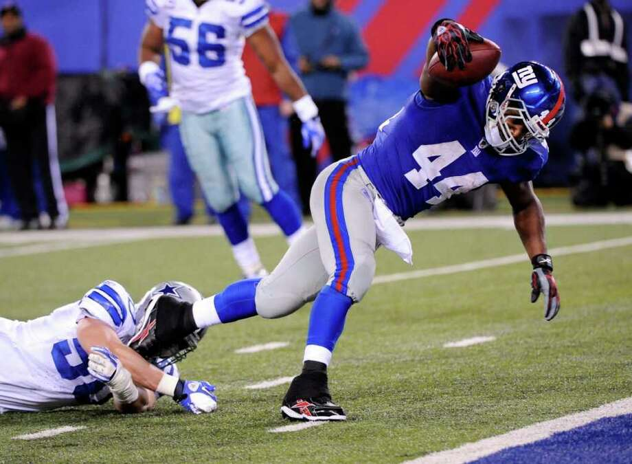 New York Giants running back Ahmad Bradshaw (44) evades a tackle by Dallas Cowboys Sean Lee to score on a 10-yard touchdown pass during the first half of an NFL football game Sunday, Jan. 1, 2012, in East Rutherford, N.J. Photo: Bill Kostroun, Associated Press