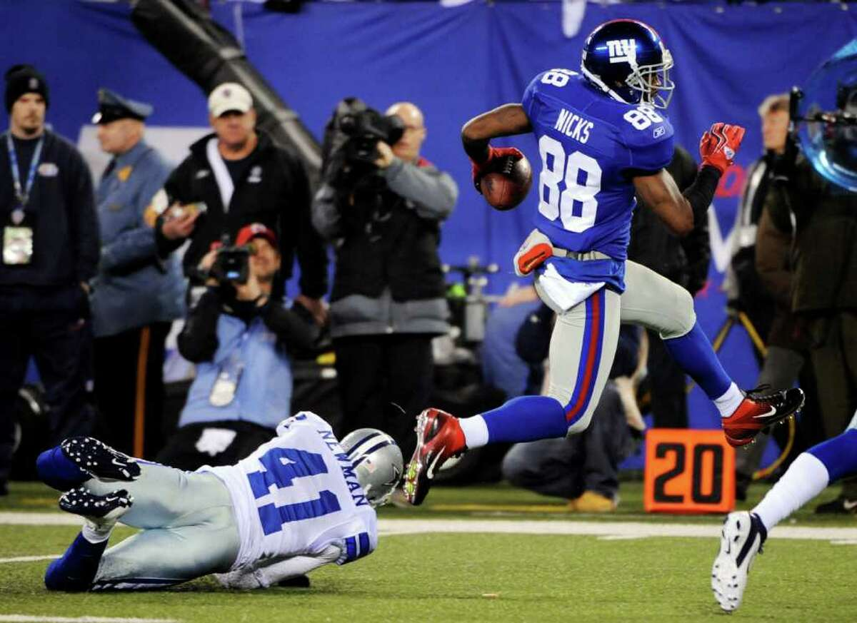 New York Giants wide receiver Hakeem Nicks (88) avoids a tackle by Dallas Cowboys cornerback Terence Newman (41) during the second half of an NFL football game Sunday, Jan. 1, 2012, in East Rutherford, N.J. The Giants won the game 31-14.