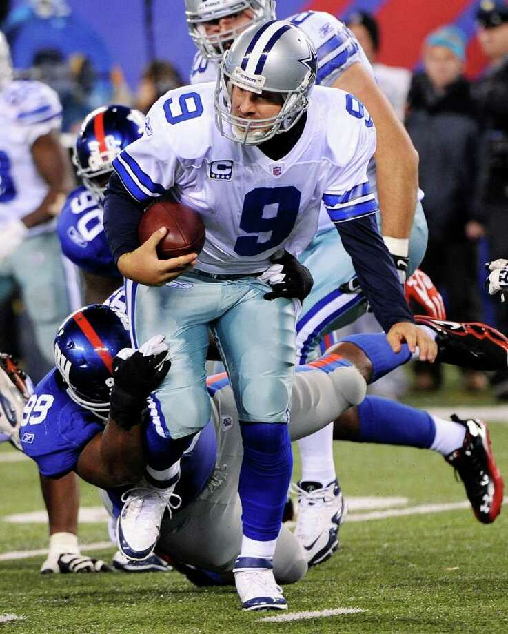 Dallas Cowboys quarterback Tony Romo (9) is tackled by New York Giants defensive tackle Chris Canty (99) during the second half of an NFL football game Sunday, Jan. 1, 2012, in East Rutherford, N.J. Photo: Bill Kostroun,  Associated Press