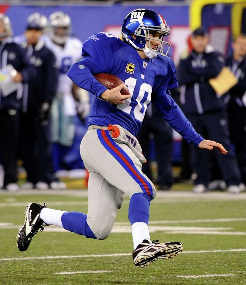 New York Giants quarterback Eli Manning scrambles with the ball against the Dallas Cowboys during the second half of an NFL football game Sunday, Jan. 1, 2012, in East Rutherford, N.J. Photo: Bill Kostroun, Associated Press