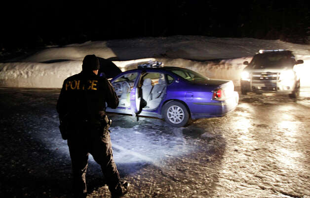 In this pool photo provided by the Pierce Co. Sheriff's Dept., a police officer examines a car on a road at Mount Rainier National Park, Sunday, Jan. 1, 2012, in Washington state. The car is believed to have been driven by Benjamin Colton Barnes, who officials say is a person of interest in the fatal shooting of a park ranger at the park Sunday morning. (AP Photo/Pierce Co. Sheriff's Dept., Ed Troyer)