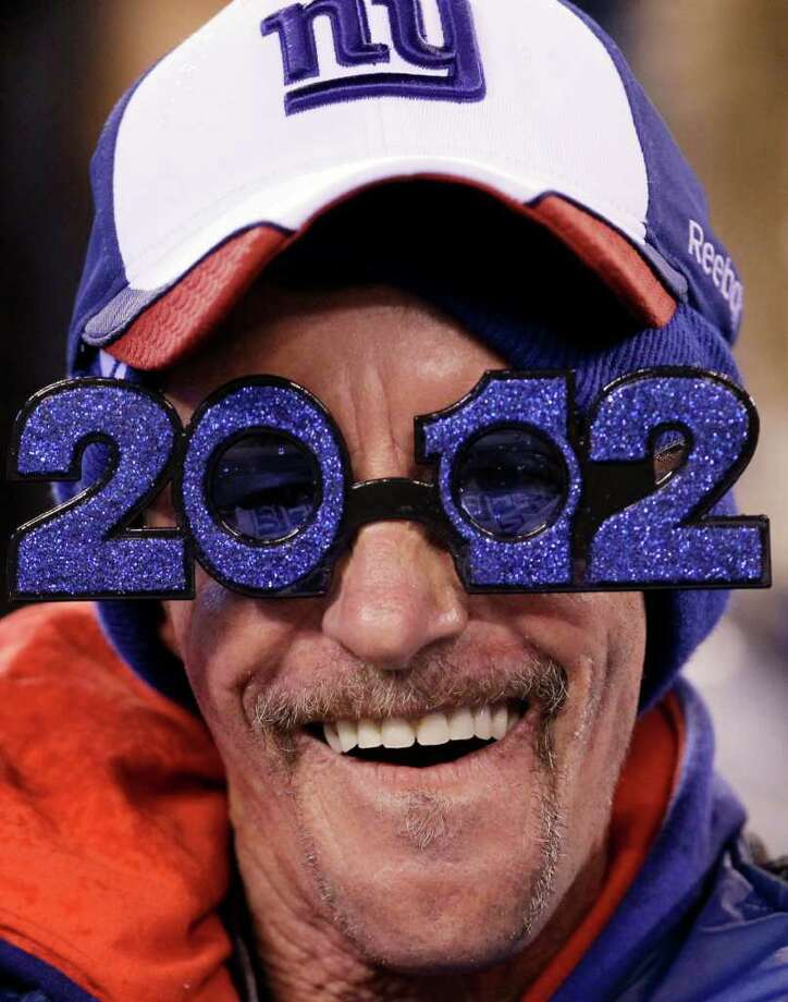 A New York Giants' fan wears 2012 glasses while watching the first half of an NFL football game between the Dallas Cowboys and the New York Giants Sunday, Jan. 1, 2012, in East Rutherford, N.J. Photo: Julio Cortez, Associated Press