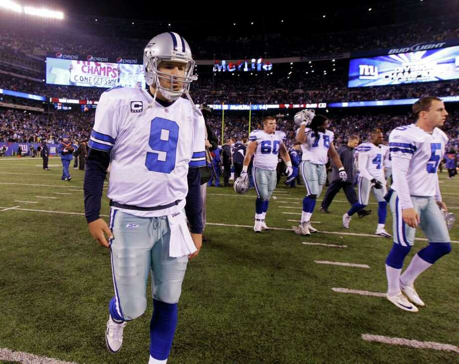 Dallas Cowboys quarterback Tony Romo walks off the field with his teammates following their NFL football game against the New York Giants Sunday, Jan. 1, 2012, in East Rutherford, N.J. The Giants defeated the Cowboys 31-14. Photo: Julio Cortez, Associated Press