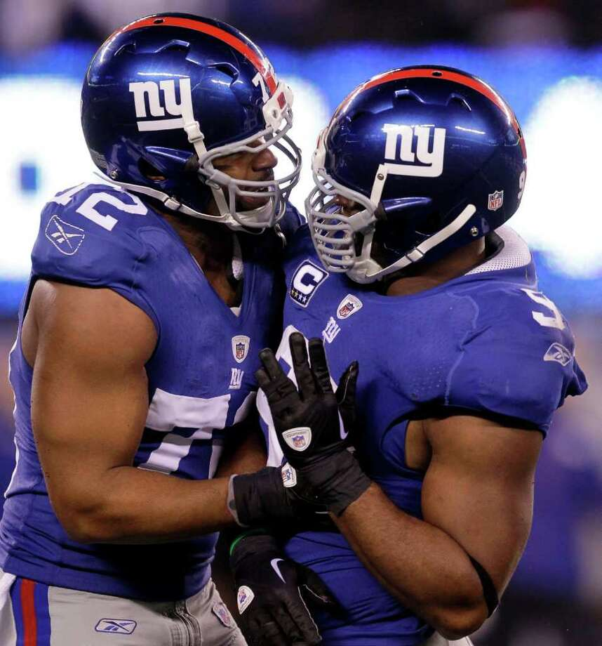 New York Giants defensive end Justin Tuck, right, is congratulated by  Osi Umenyiora after Tuck sacked Dallas Cowboys quarterback Tony Romo during the second half of an NFL football game Sunday, Jan. 1, 2012, in East Rutherford, N.J. The Giants defeated the Cowboys 31-14. Photo: Julio Cortez, Associated Press