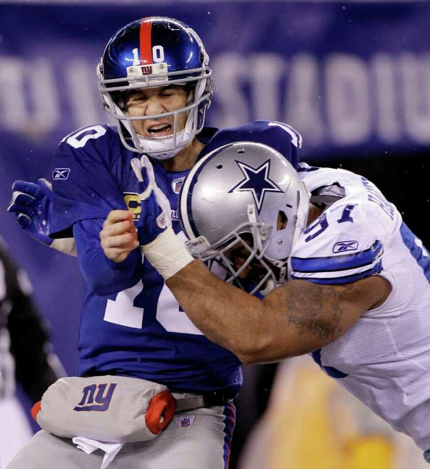 New York Giants quarterback Eli Manning grimaces while being hit by Dallas Cowboys defensive end Jason Hatcher (97) during the first half of an NFL football game Sunday, Jan. 1, 2012, in East Rutherford, N.J. Photo: Kathy Willens, Associated Press