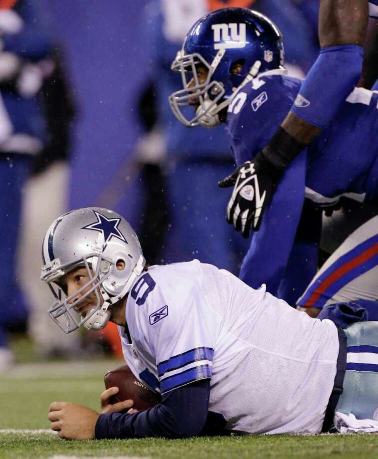 Dallas Cowboys quarterback Tony Romo lies on the field after getting sacked by New York Giants middle linebacker Jacquian Williams, right, during the first half of an NFL football game Sunday, Jan. 1, 2012, in East Rutherford, N.J. Photo: Kathy Willens, Associated Press
