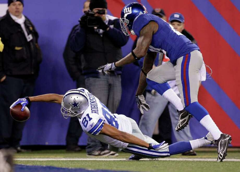 Dallas Cowboys wide receiver Laurent Robinson (81) reaches out to score on a 34-yard touchdown pass against New York Giants safety Kenny Phillips during the second half of an NFL football game Sunday, Jan. 1, 2012, in East Rutherford, N.J. Photo: Kathy Willens, Associated Press