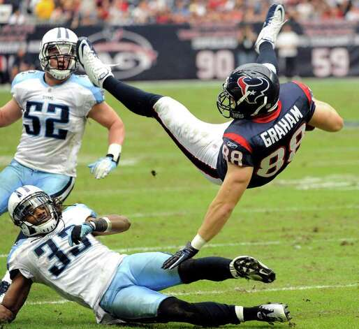 Houston Texans tight end Garrett Graham (88) is upended by Tennessee Titans free safety Michael Griffin (33) as Titans' Colin McCarthy (52) watches in the third quarter of an NFL football game on Sunday, Jan. 1, 2012, in Houston. The Titans won 23-22. Photo: Dave Einsel, Associated Press