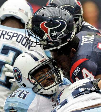 Houston Texans running back Ben Tate (44) loses his helmet as he runs over Tennessee Titans strong safety Jordan Babineaux (26) to score a touchdown in the first quarter of an NFL football game, Sunday, Jan. 1, 2012, in Houston. Photo: David J. Phillip, Associated Press