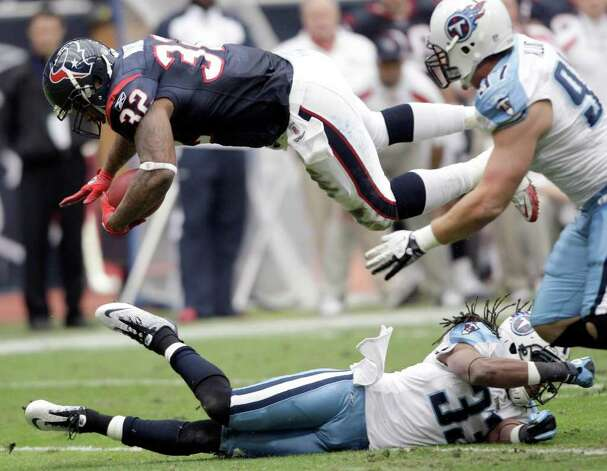 Houston Texans running back Derrick Ward (32) dives over Tennessee Titans free safety Michael Griffin (33) for a first down in the first quarter of an NFL football game on Sunday, Jan. 1, 2012, in Houston. Photo: David J. Phillip, Associated Press