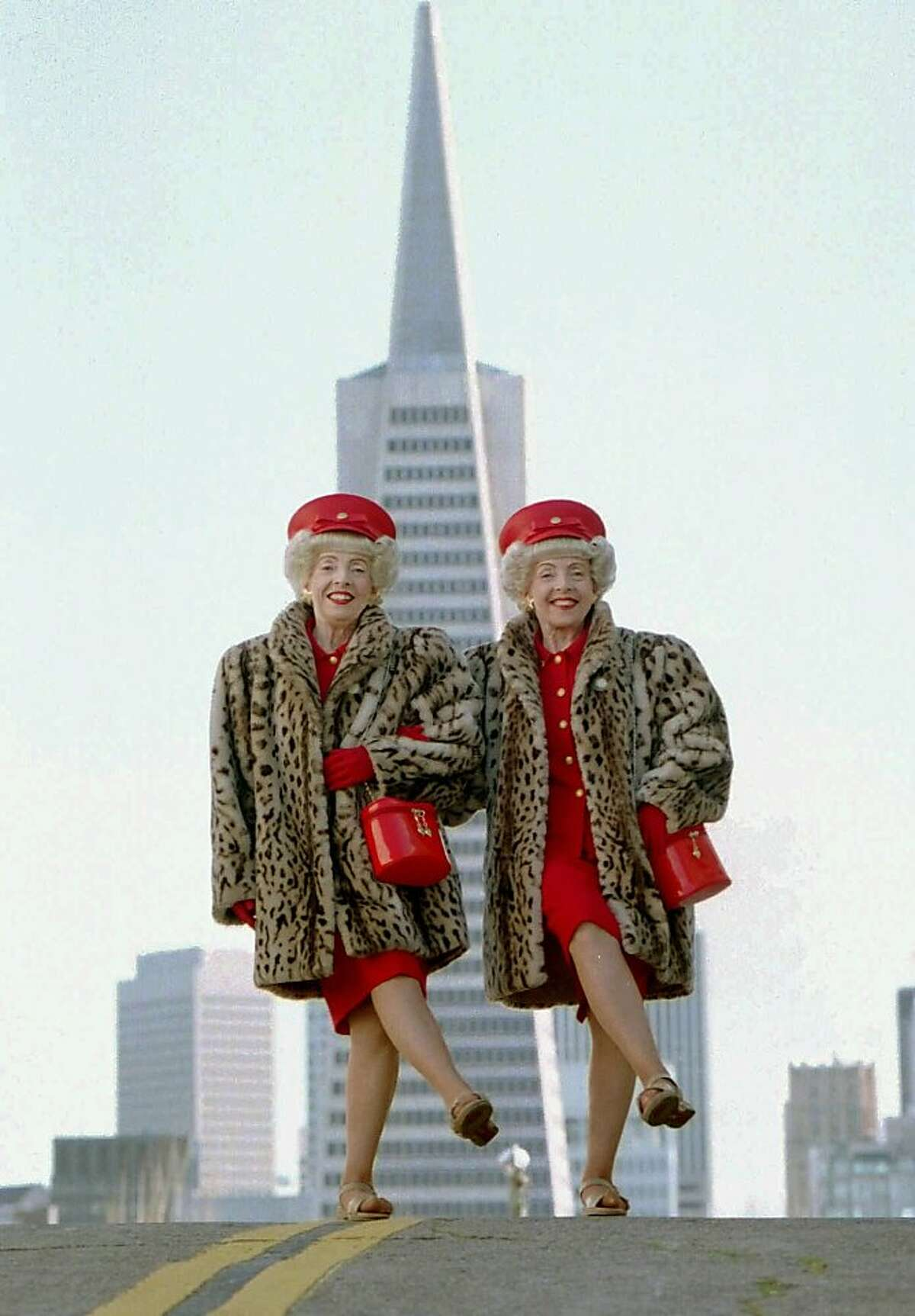 Vivian, left, and Marian Brown, identical twins, shake a leg in front of the Transamerica building. Although they were born and raised in Michigan, the Browns have become icons of San Francisco--they took second place in 2000 as the city's