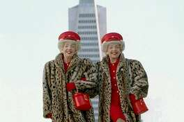 """Vivian, left, and Marian Brown, identical twins, shake a leg in front of the Transamerica building. Although they were born and raised in Michigan, the Browns have become icons of San Francisco--they took second place in 2000 as the city's """"Best Local Character."""""""
