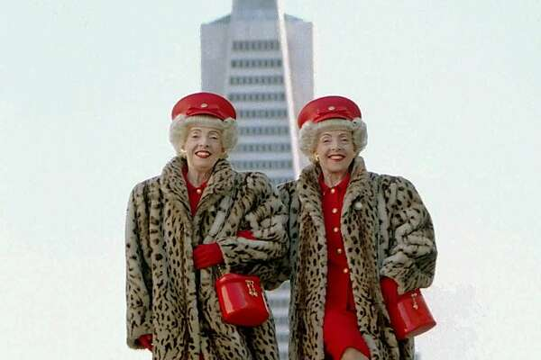 "Vivian, left, and Marian Brown, identical twins, shake a leg in front of the Transamerica building. Although they were born and raised in Michigan, the Browns have become icons of San Francisco--they took second place in 2000 as the city's ""Best Local Character."""