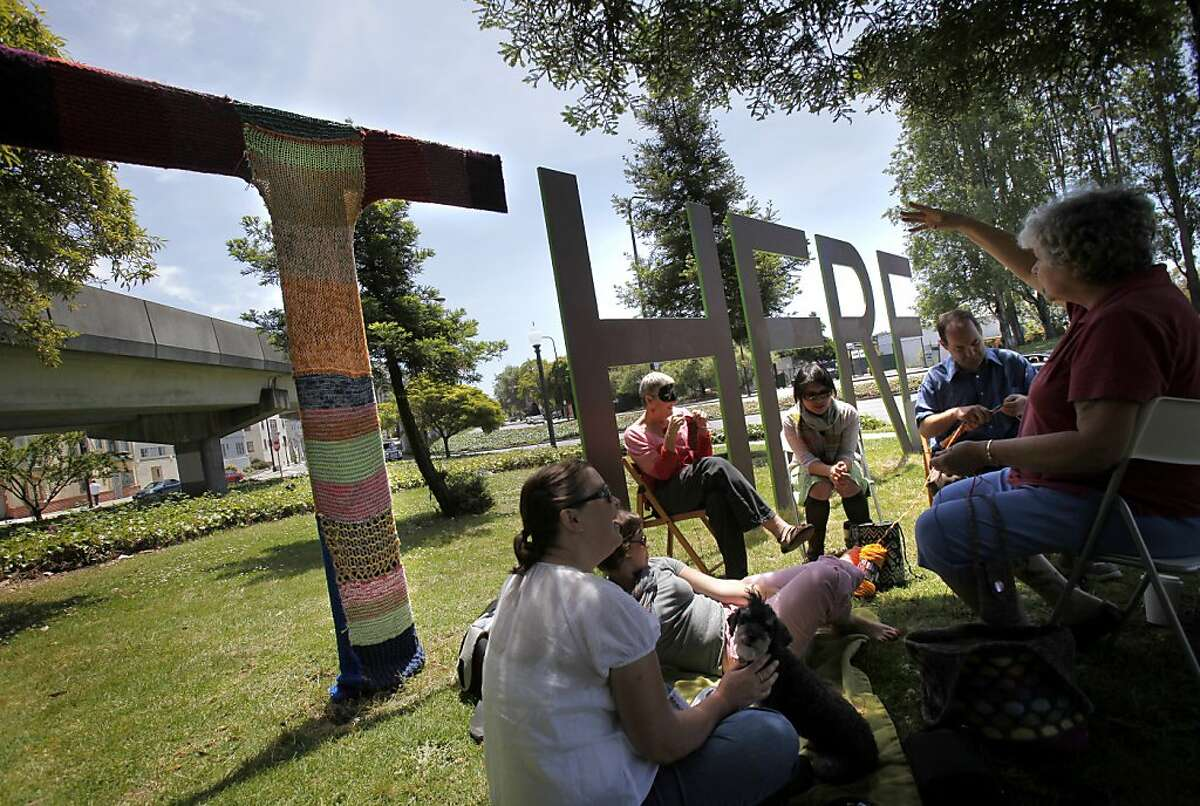 """A group of knitters from Oakland have covered the """"T"""" of the """"There/Here"""" sculpture between Berkeley and Oakland with yarn to protest the artwork, which they feel bashes Oakland."""