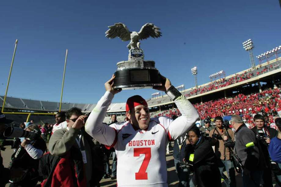 University of Houston quarterback Case Keenum (7) walks off the field with the Ticket City Bowl trophy after beating Penn State 30-14 Monday, Jan. 2, 2012, in the Cotton Bowl Stadium in Dallas. Photo: Nick De La Torre, Chronicle / © 2012  Houston Chronicle