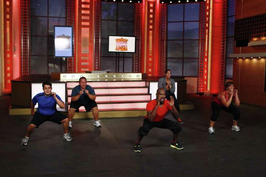 Dolvett Quince, center, an Atlanta-based personal trainer, leads a team of former contestants in a scene from the at-home exercise DVD 'The Biggest Loser: At Home Challenge.' Quince, a former Stamford and Bridgeport resident, is in his second season on NBC's 'The Biggest Loser.' The 13th season of the show premieres on Tuesday, Jan. 3.  Contributed photo/Lionsgate Home Entertainment Photo: Contributed Photo