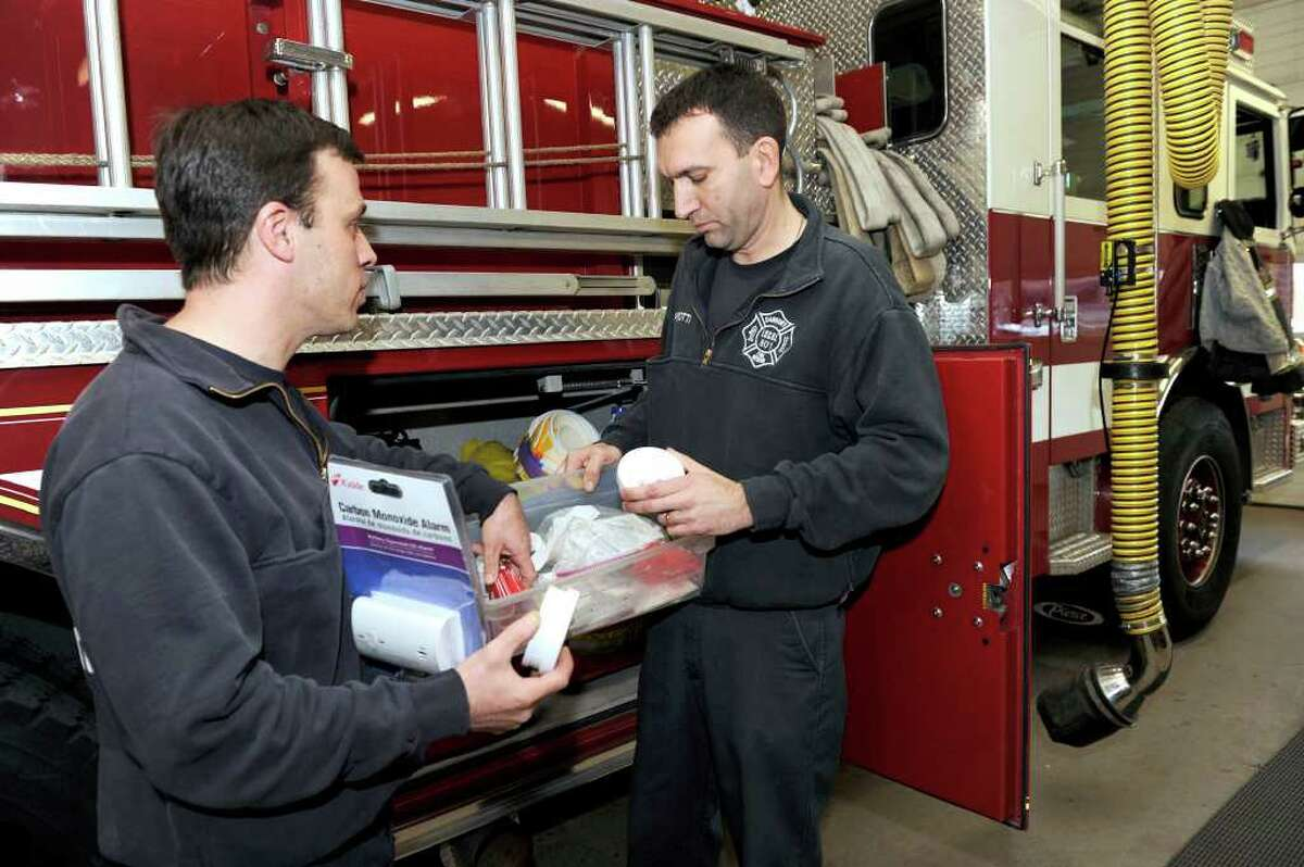 Danbury firefighters Rich Krikorian, left, and Paul Perrotti, are photographed with some of the smoke and carbon monoxide detectors that are kept on fire department vehicles. The devises are made available, when on fire calls, it's found that a homeowner doesn't have one. Photo taken Monday, Jan. 2, 2012.