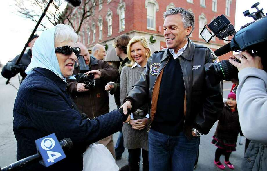 Republican presidential candidate, former Utah Gov. Jon Huntsman, accompanied by his wife Mary Kaye, stops to shake hands while touring businesses in downtown Nashua, N.H., Monday, Jan. 2, 2012.  (AP Photo/Cheryl Senter) Photo: Cheryl Senter, Associated Press / FR62846 AP