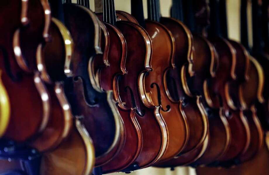 A row of violins hangs from Antonio Strad Violin, a local shop. A new study pits Stradivari and del Gesu violins against new instruments. Photo: KIN MAN HUI, San Antonio Express-News / kmhui@express-news.net